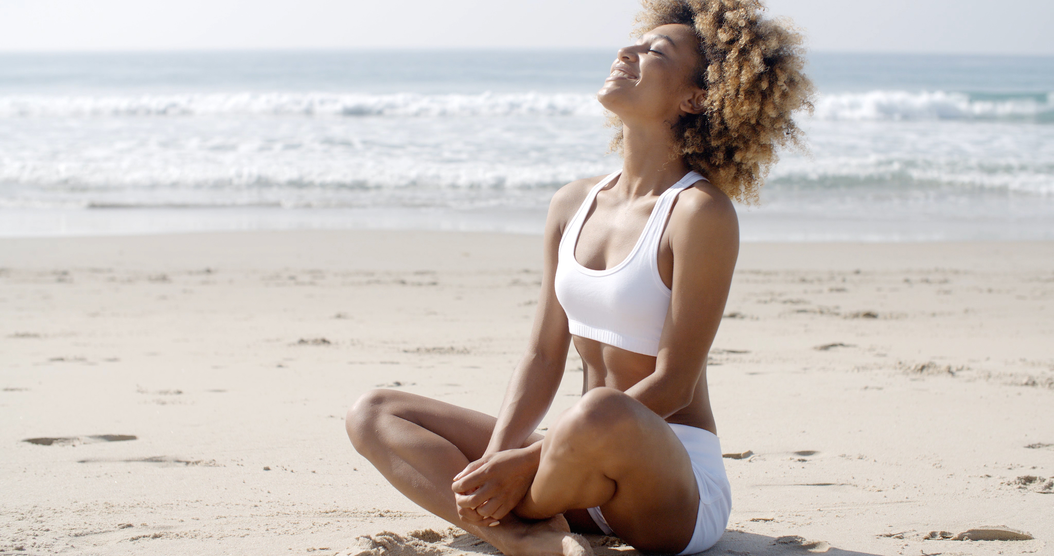 Woman Meditating On Beach In Lotus Position